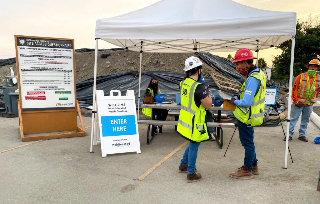 construction workers standing outside a mobile-med tent