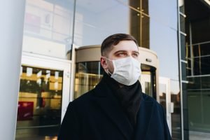 professional man outside a building wearing a mask