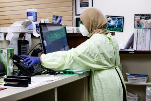 nurse wearing protective gear at a computer workstation