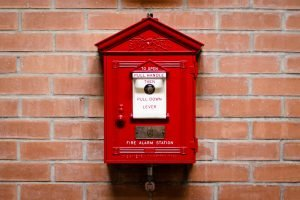 fire alarm station hanging on a brick wall