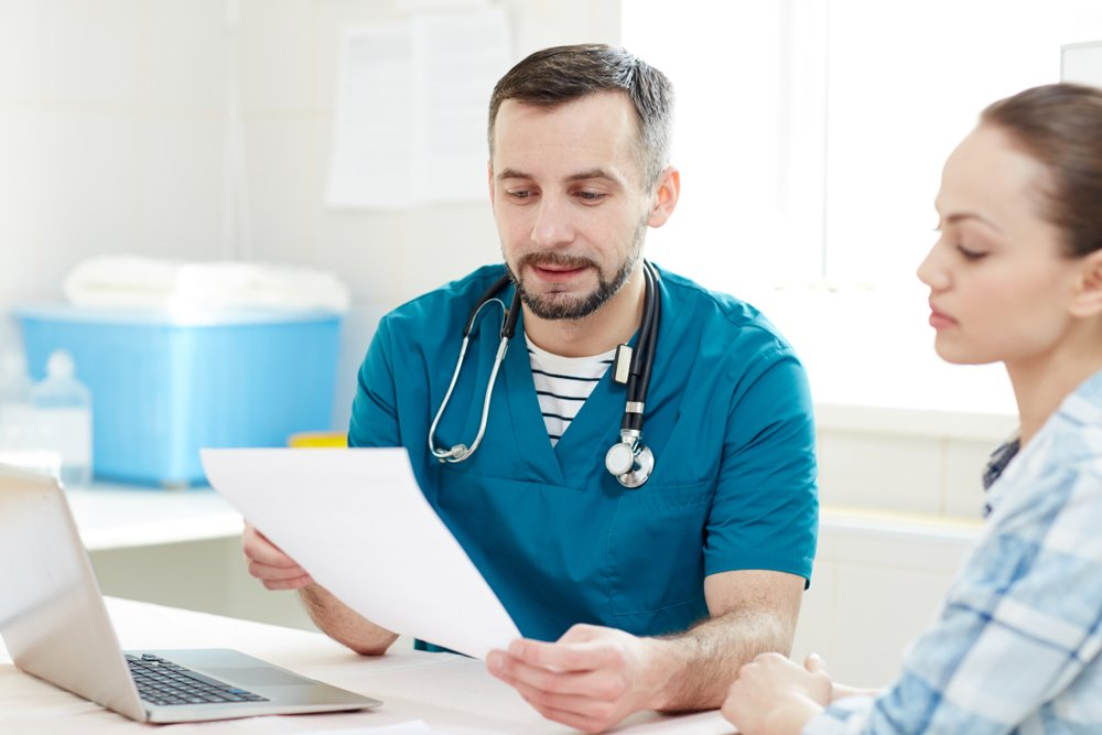 clinician and a woman looking at a piece of paper