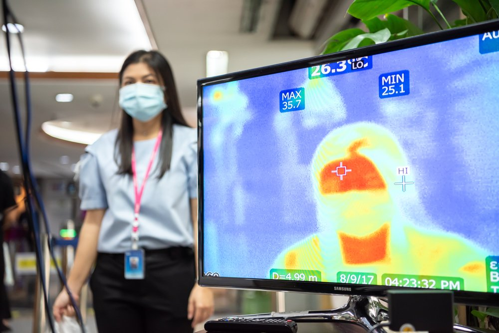 woman standing next to thermographic screen