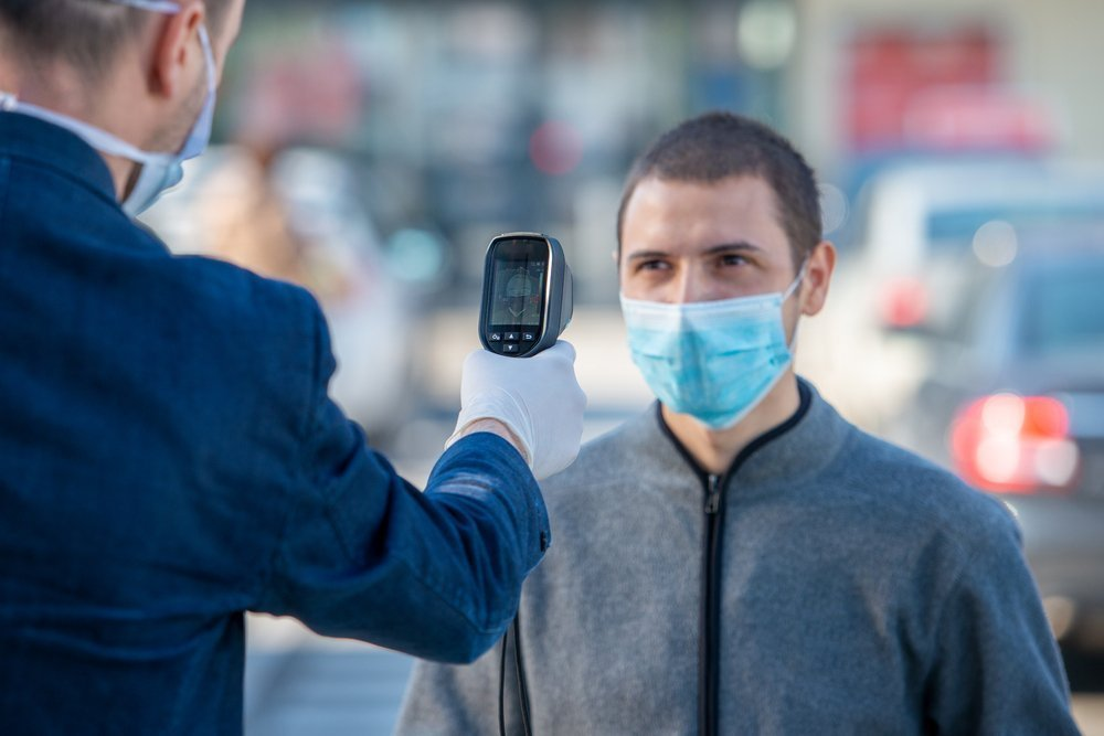 man taking another man's temperature